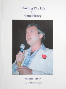 """The cover of the book """"Charting the life of Gene Pitney"""" by Michael Turner including a photograph of Gene Pitney singing into a microphone"""